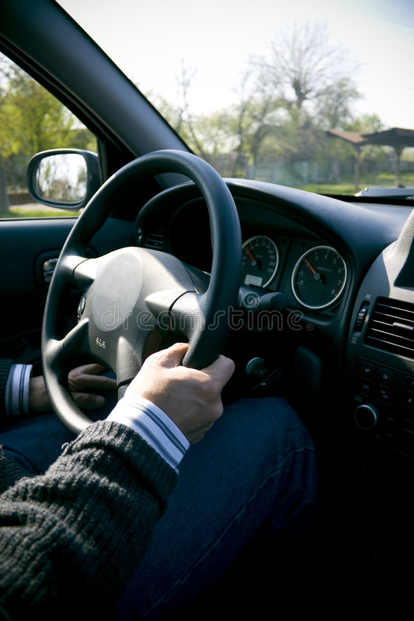 Car Interior. As seen from passenger seat, steering wheel with hand on it and dashboard and windshield royalty free stock photo