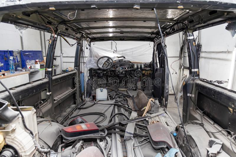 Car interior in the back of a van with a disassembled lining, seats removed, spare parts lying on the floor glass and rubber seal royalty free stock photo