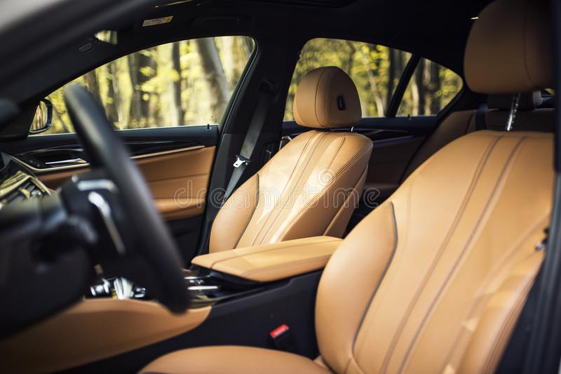 Car Interior: Beige Leather Front Car Seats. Premium beige leather car seats located in the front of a luxury modern car. Featuring premium leather materials and stock photography