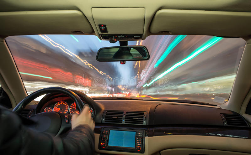 Car interior on driving. Blurred night lights royalty free stock image