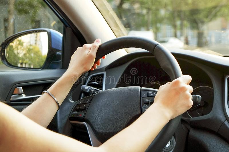Car interior with female driver sitting behind the wheel, soft sunset light. Luxurious vehicle dashboard and electronics. royalty free stock images