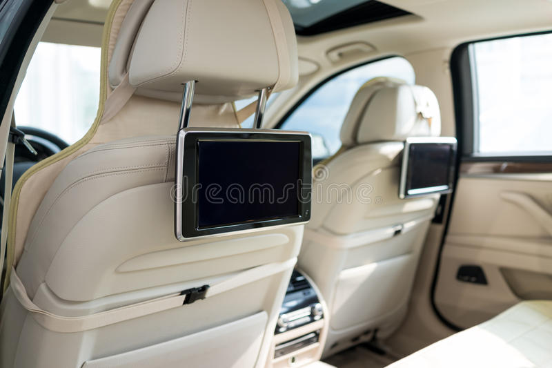 Car interior. LCD screen hanging on the back of the seat royalty free stock photography