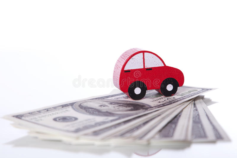 Car investment. Red car over a lot of dollar bills isolated on white (selective focus stock photo