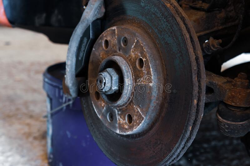 Car on a jack without a wheel. Brake pad replacement, car repair stock images