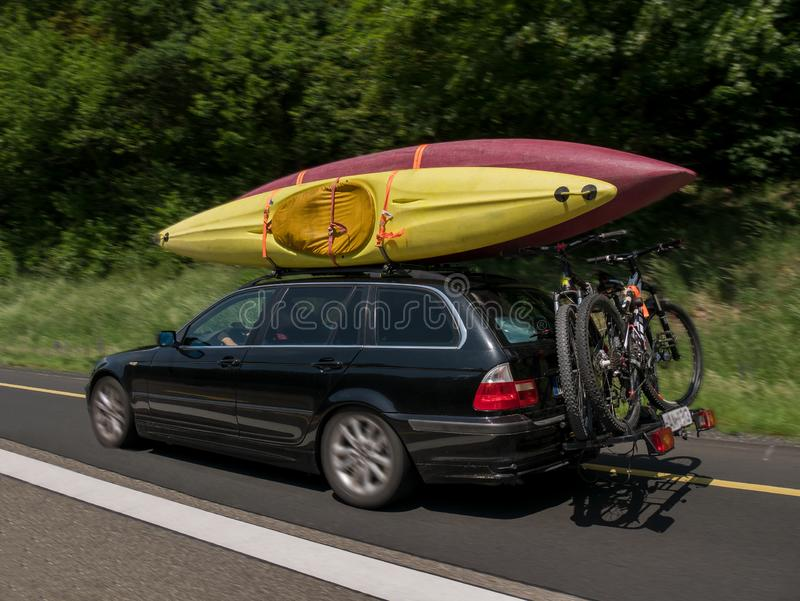 Car with kayaks on the top and bicycles on the back going for holiday royalty free stock photography