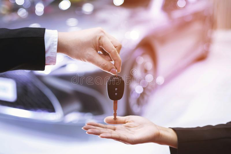 Car key, businessman handing over gives the car key to the other woman on car background. Car key, businessman handing over gives the car key to the other woman stock photo