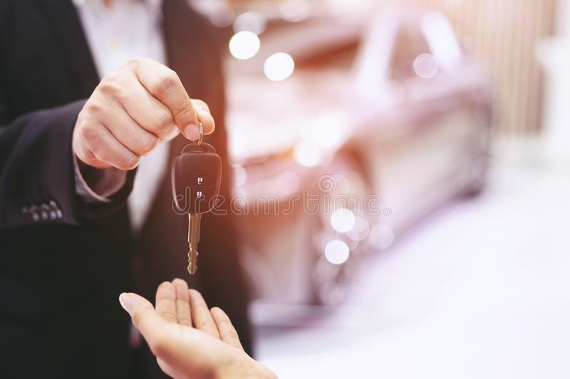 Car key, businessman handing over gives the car key to the other woman on car background. Leave a space for writing descriptive text royalty free stock photo