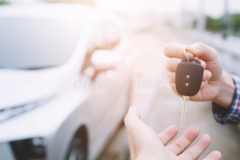 Car key, businessman handing over gives the car key to the other woman. On car background royalty free stock photos