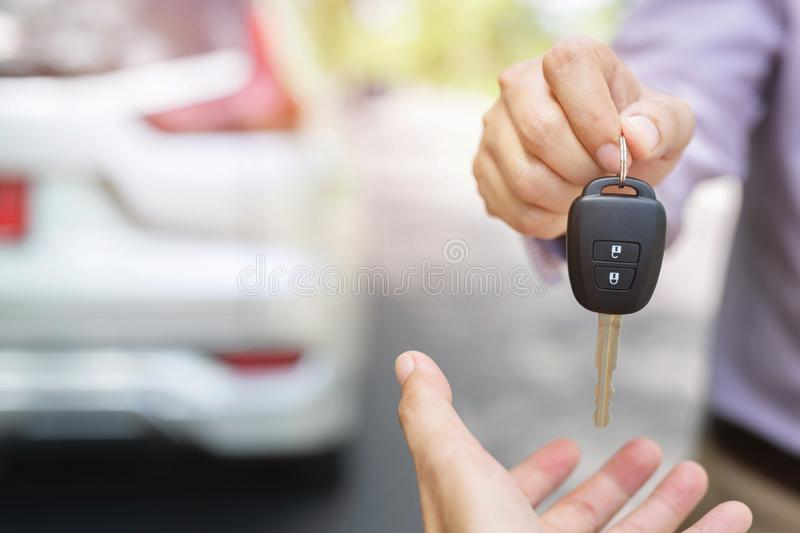 Car key, businessman handing over gives the car key to the other woman. On behind the new car background. transportation and vehicle concept royalty free stock photo