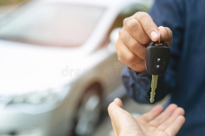Car key, businessman handing over gives the car key to the other woman. On car background stock photography