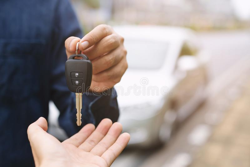 Car key, businessman handing over gives the car key to the other woman on car background. Leave space to write messages. Car key, businessman handing over gives royalty free stock photo