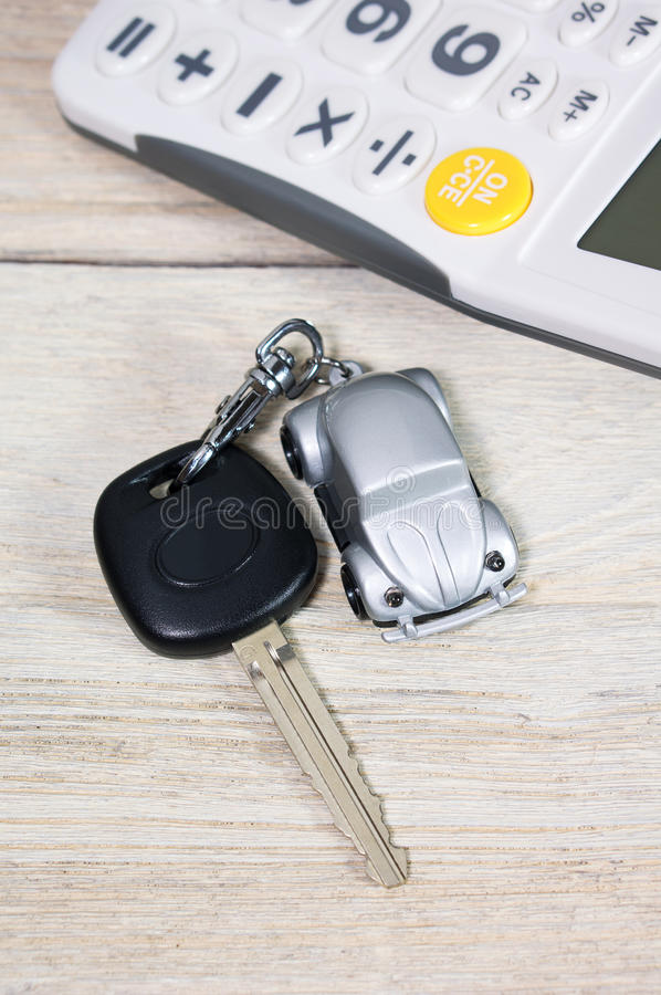 Car key with calculator. On wood table royalty free stock images