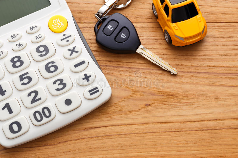 Car key with calculator. On wood table stock image