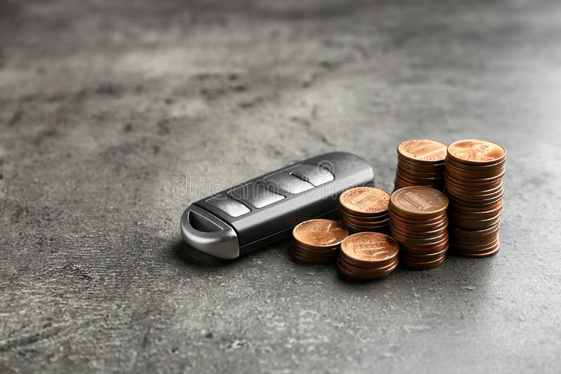 Car key and coins on grey background. stock photos