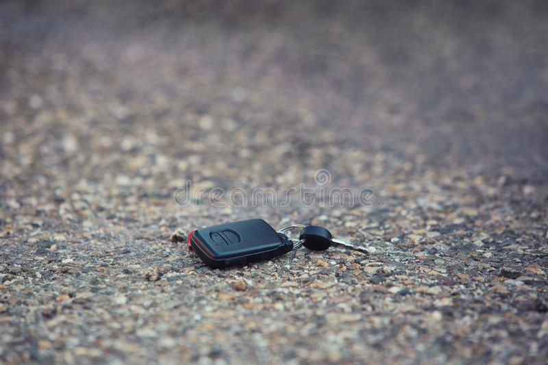 Car key fall on the asphalt road. Driver lost his vehicle keys. Misfortune concept stock images