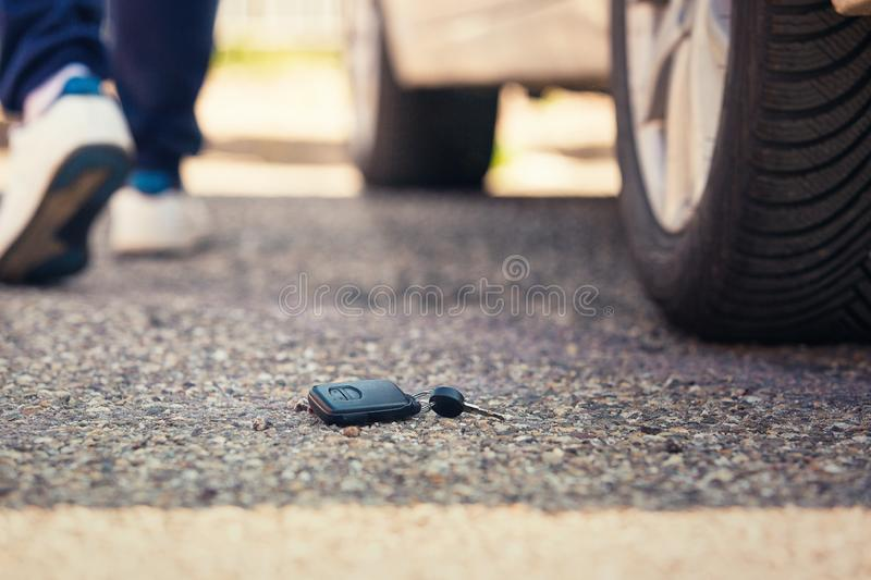 Car key fall on the asphalt road. Driver lost his vehicle keys and walks away. Misfortune concept stock photos