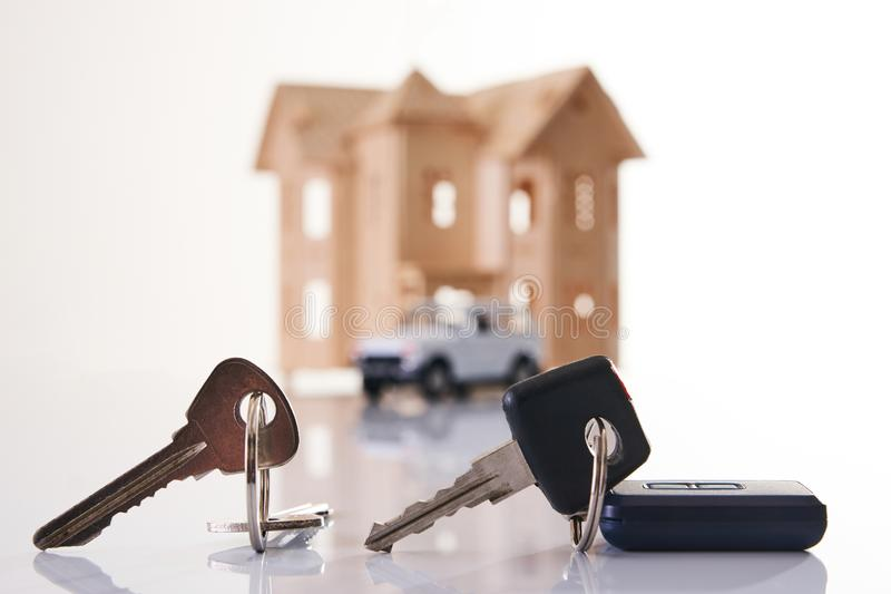Car key and house keys with new automobile and home stock photography