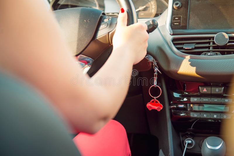 Car key in ignition. Start, stop or accelerate engine. Car shape keyfob on vehicle dashboard background during driving. Woman. Driver. Selective focus, Copy stock photo