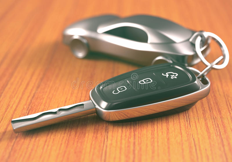 Car Key Keychain. Car key with a car shaped keychain, on a wooden table stock image