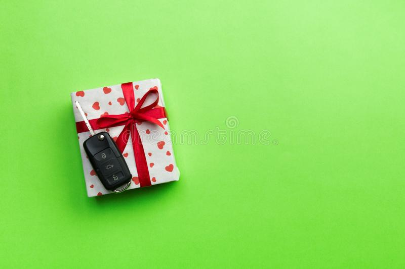 Car key on paper gift box with red ribbon bow and heart on green table background. Holidays present top view concept royalty free stock photography