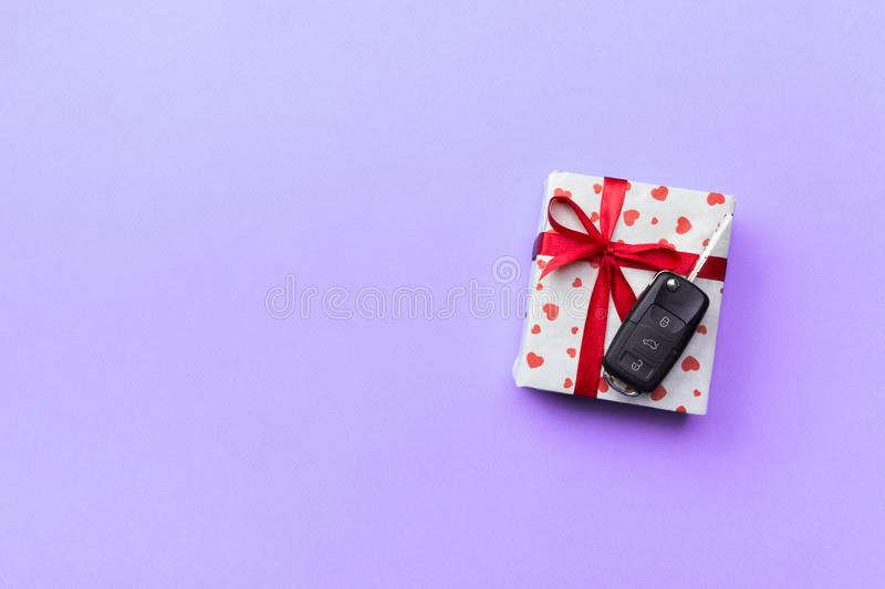 Car key on paper gift box with red ribbon bow and heart on violet table background. Holidays present top view concept royalty free stock image