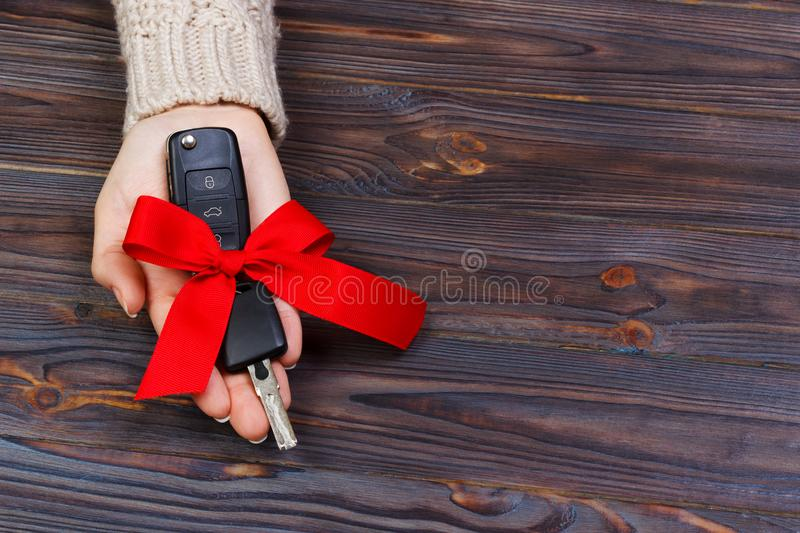 Car key with red bow in woomen hand on wooden background. Valentine`s Day concept.  stock photography