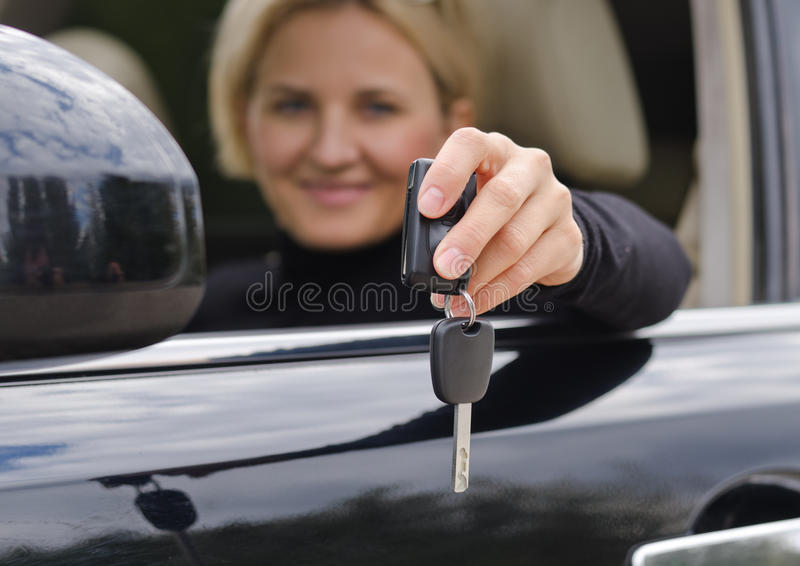 Car key. Smiling blonde woman holding a car key inside the car royalty free stock images