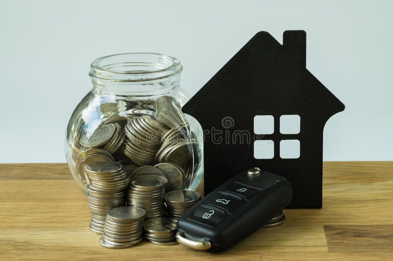 Car key, stack of coins and coins in glass jar with paper house stock images