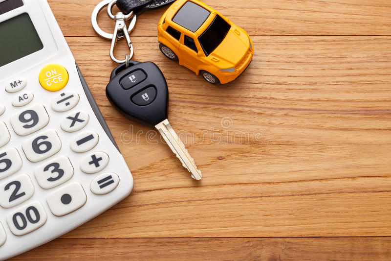Car key on wood background. Car key with calculator on wood table background stock photography