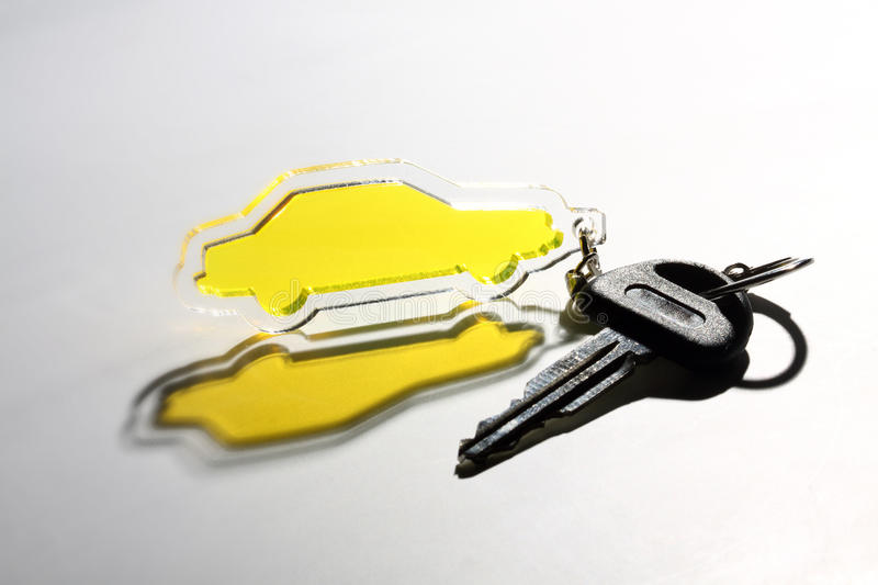Car keychain. Yellow transparent car keychain and key stock photography