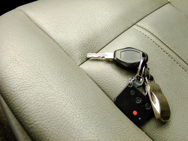 Car Keys on the Front Seat. Car Keys with Alarm Remote and Pendant on the Background of Front Leather Seat of A luxury Car royalty free stock images