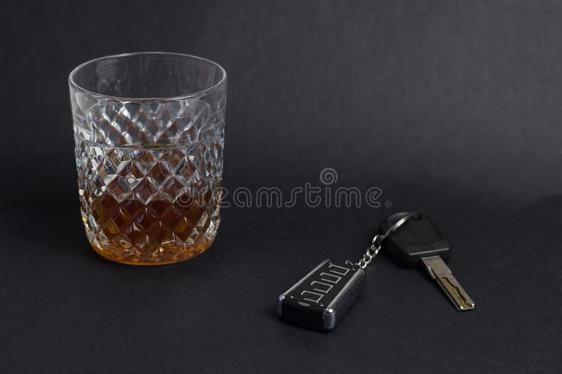 Car keys and glass with alcohol whiskey on black background, close-up. Drunk royalty free stock photos