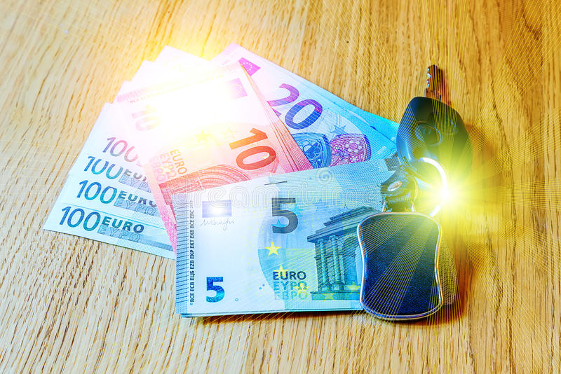 Car keys lay on the euro banknotes and wooden table. Car keys lay on euro banknotes and wooden table royalty free stock photography