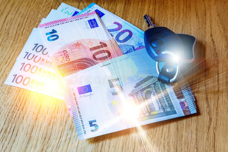 Car keys lay on the euro banknotes and wooden table. Car keys lay on euro banknotes and wooden table royalty free stock image