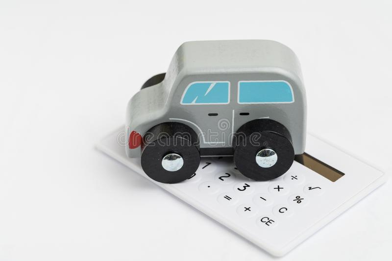 Car leasing, insurance or purchase calculation, maintenance cost concept, miniature toy wooden car on small calculator on white royalty free stock photography