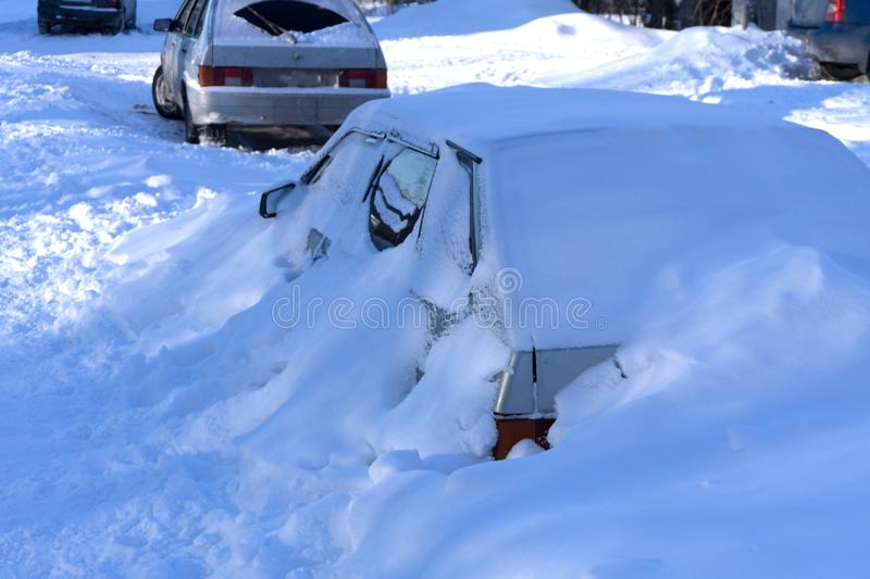 A car left by its owner in the open air for the winter was covered with a large layer of snow . stock photos