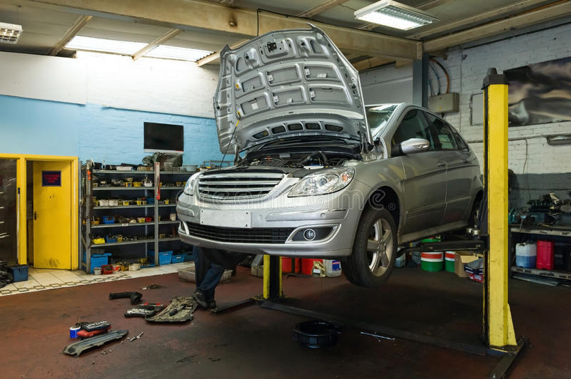 Car on a lift in garage. Car inspection on a service lift in a garage stock photos