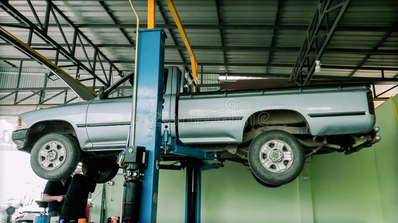 Car lifted in Manual pickup truck.Professional Technician  mechanic worker service  center for fixing repairs change engine oil.  royalty free stock images