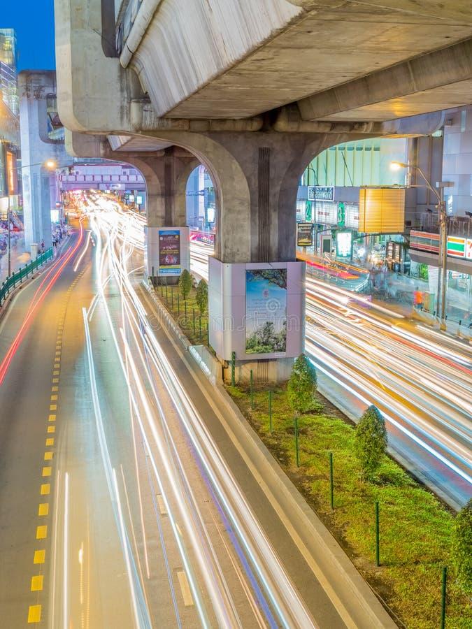 Car light movement in Bangkok. BANGKOK - AUGUST 8: Movement of car light on traffic road at Siam Square shopping center in Bangkok under twilight evening sky royalty free stock photo