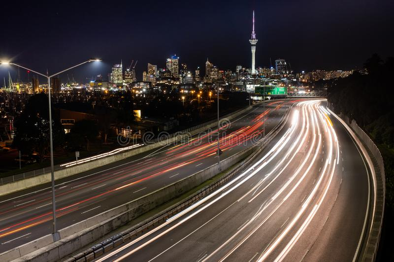 Car light trails at night heading into Auckland, with the city skyline royalty free stock image