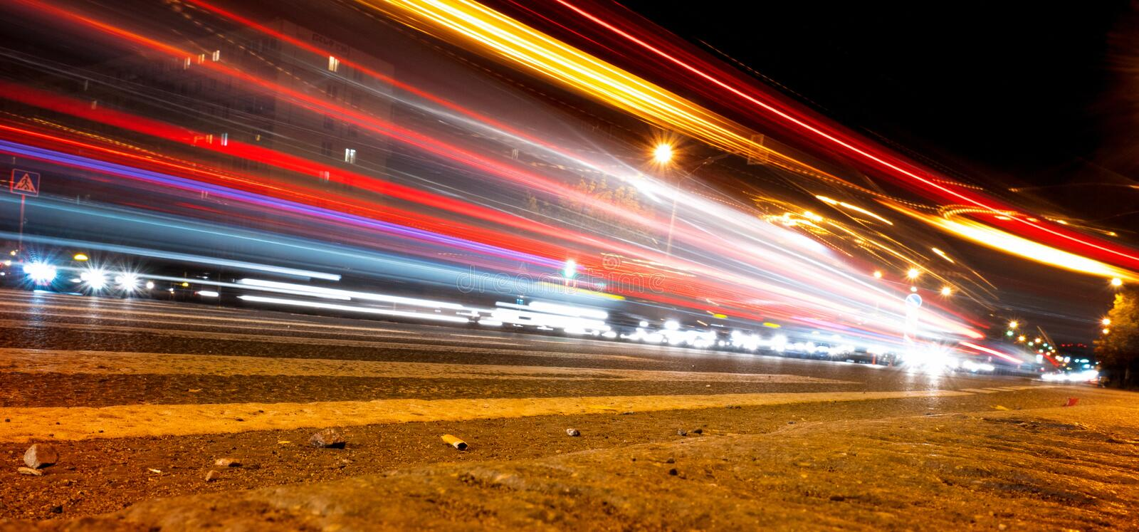 Car light trails on the street near road bridge, people walking in fast motion, night street background. Car light trails on the street near road bridge, people stock photos