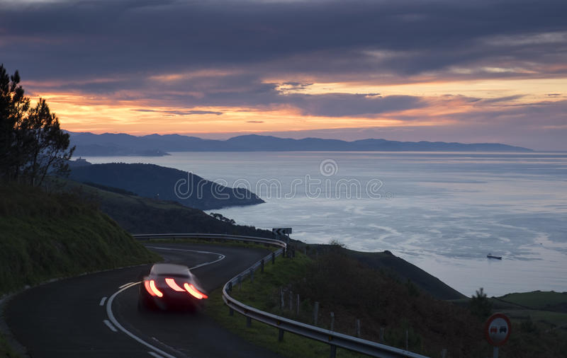 Car lights in the road, Basque coast. stock image