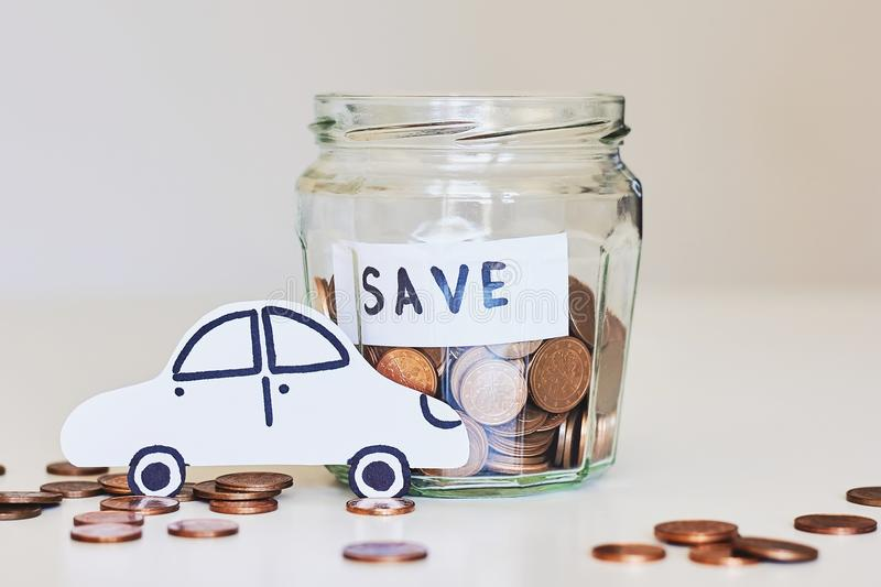 Car loan, car insurance concept. Glass jar full of coins and white paper car royalty free stock photography