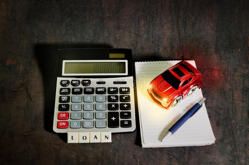 Car loan concept,planning to buy a car. Car loan concept, a calculator beside the spiral notebook with pen and red toy car stock photo