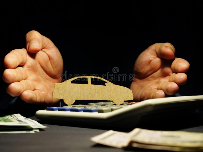 Car loan. Hands offers model of vehicle. On a calculator royalty free stock photos