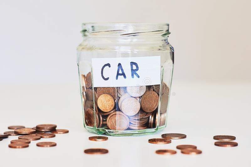Car loan, car insurance concept. Glass jar full of coins and paper sign car royalty free stock photos