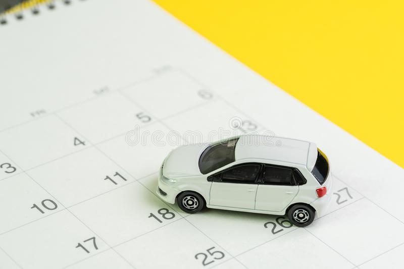 Car loan payment, buying new car or yearly maintenance schedule concept, miniature white car on clean calendar with date on yellow. Background stock photos