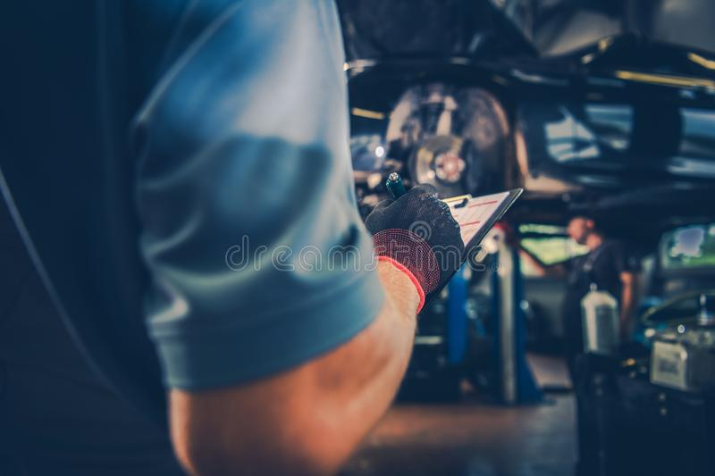 Car Maintenance Check List. Vehicle Maintenance Check List. Car Mechanic with Documentation in Hand. Automotive Industry Theme stock photography