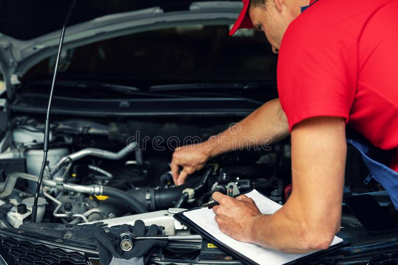Car maintenance - mechanic check the engine and writing in checklist stock photography