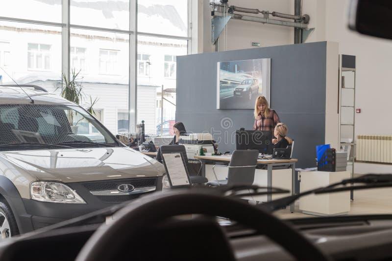 Car and manager in showroom of dealership AVTOVAZ named SeverAvto in Kirov city in 2018. Top view. Kirov, Russia - March 06, 2018: Cars and manager in showroom royalty free stock photo